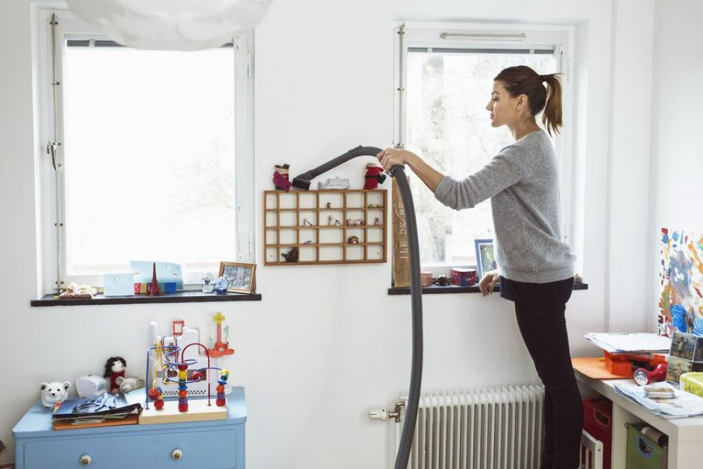 woman vacuuming inside kids room